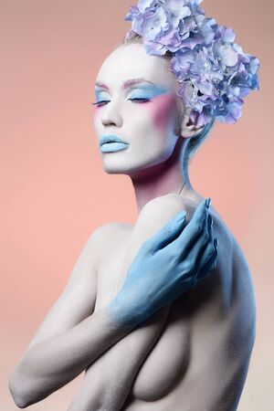 Beautiful naked girl with Blue Flowers and art make-up. Fairy beauty young woman in paint. Body art Stockfoto