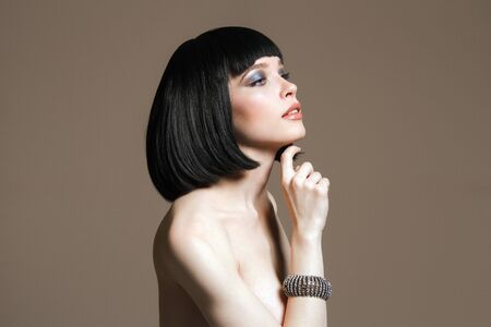 Beautiful girl with Bob Hairstyle and make-up. Naked beauty young woman with jewelry bracelet on her hand Stock Photo