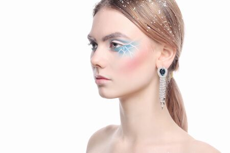 fashion beauty portrait of young woman with make-up and snow on her hair. beautiful model girl with color paint makeup