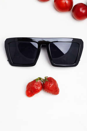 abstract still life. sunglasses and berries like a male face with mustache