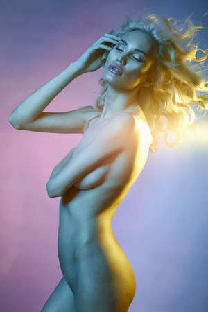 beautiful naked girl with curly hair in color lights. young nude body woman