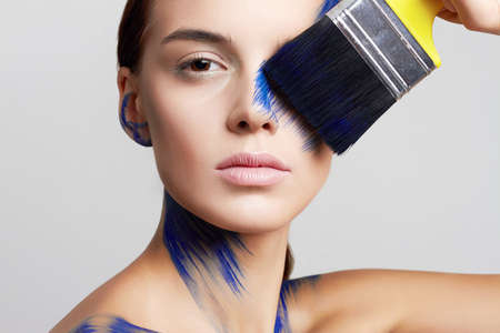Girl with paint on her Face, drawing with a brush on herself. Blue paint on beautiful face and Body. Color portrait of Woman in Paint Stockfoto