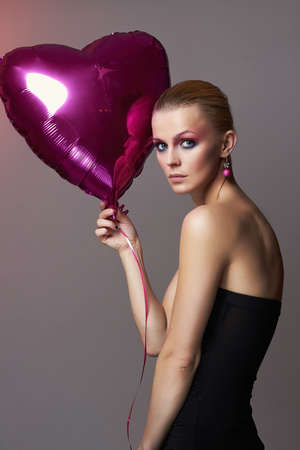 Beautiful girl with heart shaped balloon and colorful makeup. beauty fashion portrait. young woman with Make-up. valentines day Stockfoto