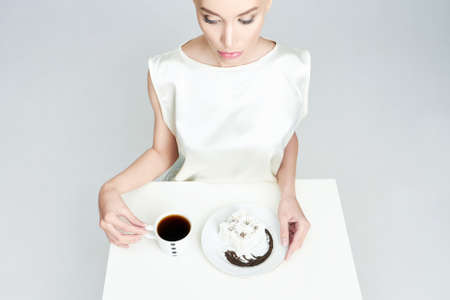 Fashion beauty woman with coffee and dessert. Beautiful girl in silk dress has breakfast