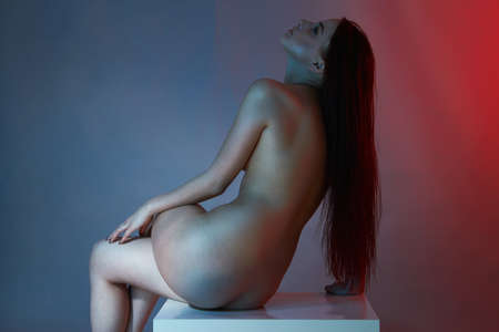 sensual beautiful naked girl in color lights. female back. sitting nude woman Stockfoto - 152315819