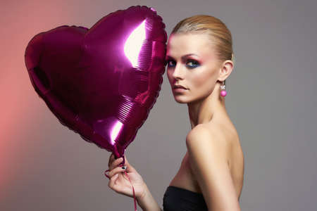 Beautiful girl with heart shaped balloon and colorful makeup. beauty fashion portrait. young woman with Make-up. valentines day Stock Photo