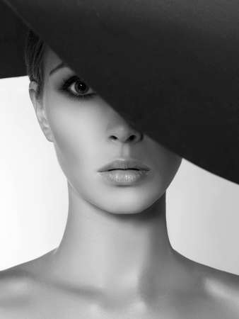 Beautiful woman in hat. black and white beauty fashion portrait