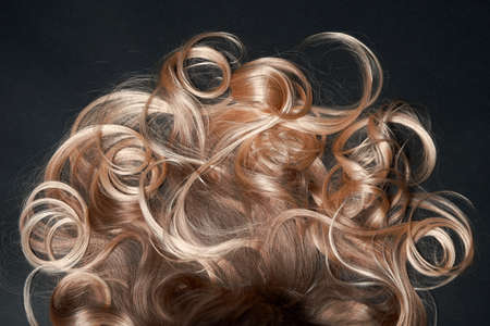 beautiful healthy blond curly female hair on a black background