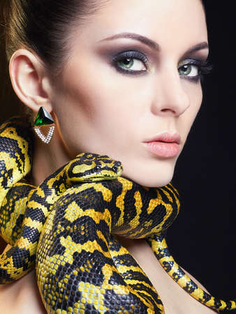 beautiful young woman with Snake. Brunette girl with fashion perfect make up. Beauty close up studio shot. jewelry earrings Stock Photo