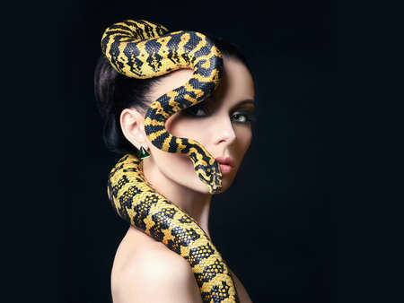 beautiful young woman with Snake on her head like a hair. Brunette model with fashion make up. Beauty close up studio shot.jewelry earrings