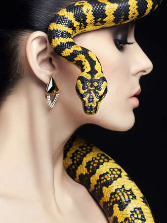 beautiful young woman with Snake. Brunette model girl with fashion make up. Beauty jewelry earrinrs