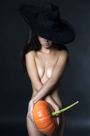 beautiful naked woman in witch hat. nude girl holding halloween pumpkin Stockfoto