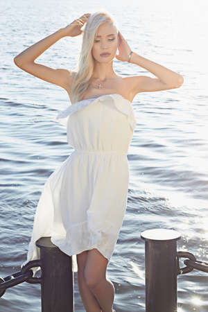 Beautiful girl standing by the water. young summer blond woman in white dress Stockfoto