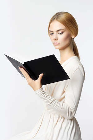 portrait of young woman with book. beautiful blond girl reading a book