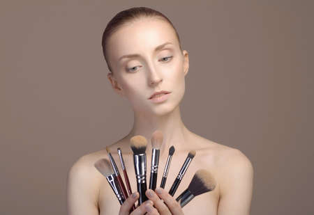 beauty portrait of young woman holding makeup brushes. beautiful model girl