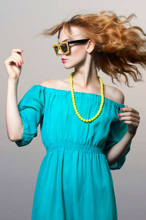 Beautiful girl in sunglasses with yellow flowers. bright young woman in motion