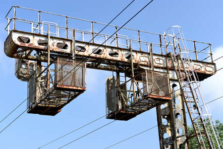 Motteville, Normandie, France, juin 2018. Electric pole with obsolescence for trains traffic lights. Pole in a poor condition, rust stains Vétusté des équipements ferroviaires SNCF. Potence de signalisation de pleine voie vétuste. Rouille. Sajtókép