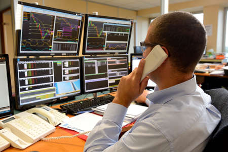 Rouen, Normandie, France, september 2015. Trading room. Negociation for futures markets. Trader with telephone.Purchase/sale orders. Computers with information of Stock Exchange & Fluctuations in the stock market.