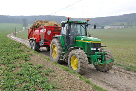 Normandy, France, March 2013. Emptying manure of dairy farming in a field as fertilizer