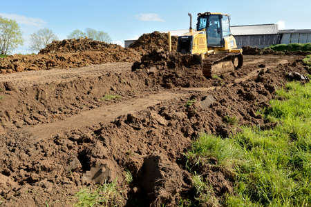Normandy, France, June 2013. Construction of a liquid manure pit in a dairy farm. Digging of the pit with an excavator and bulldozer