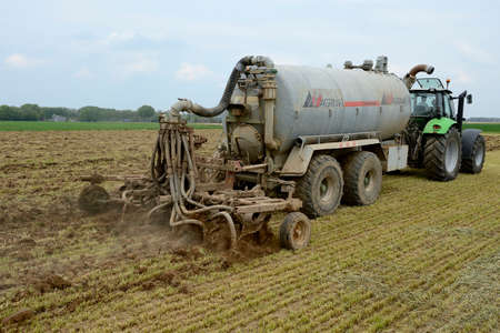 Normandy, France, May 2013. Manure spreading on a meadow with landfill. Tractor and manure tank with drag hose injector for slurry. Editorial