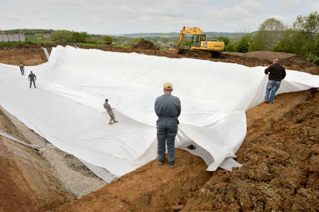 Normandy, France, June 2013. Construction of a liquid manure pit in a dairy farm. Applying polyurethane waterproofing membrane