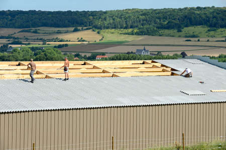 Normandy, France, July 2010. Construction of a new farm building for cows breeding with wood frame. Roofer on the roof. Installation of safety net under the roof as fall prevention. Arduous working conditions because heatwave