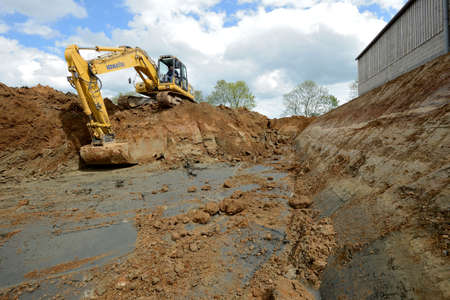 Normandy, France, June 2013. Construction of a liquid manure pit in a dairy farm. Digging of the pit with an excavator Editorial