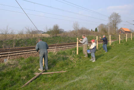 Normandy, France, April 2010. Repair of fences of a meaow along a railway to prevent the risk of livestock straying. Farmer with son and father. Family assistance Editorial
