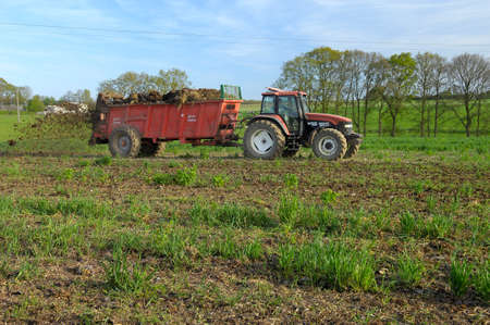 Normandy, France, JApril 2016. Spreading of manure on a field with a manure spreader