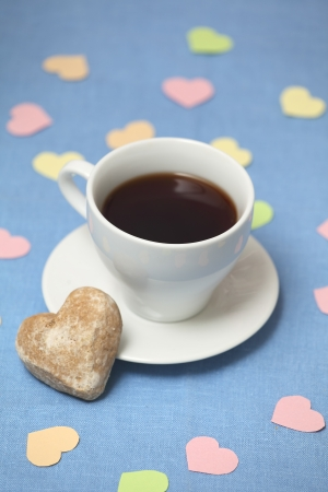 A tea cup with tea stands on the blue tablecloth with cakes all decorated with paper hearts photo