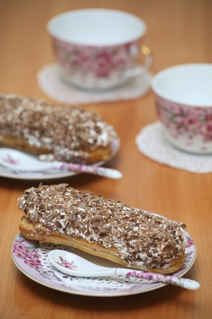 Served eclairs for a couple on a wooden table with pink cups  photo