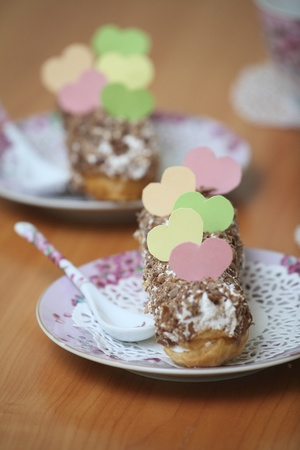 Served eclairs for a couple on a wooden table with paper hearts Stock Photo - 17286682