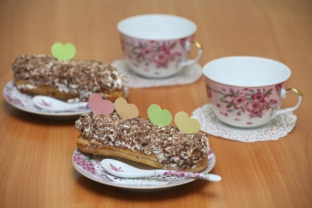 Served eclairs for a couple on a wooden table with paper hearts photo