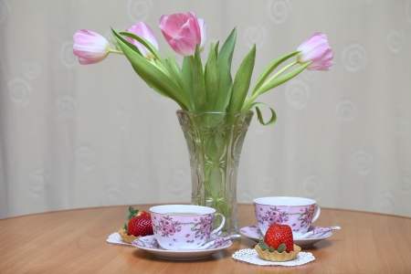Tea cups, strawberries and tulips in vase on a wooden table photo