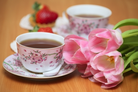 Couple of cups with tea, strawberries and tulips photo