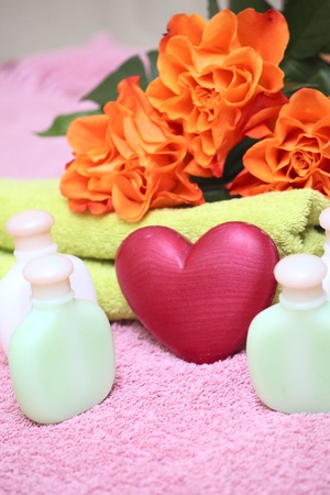 Towels, spa bottles, heart soap  and roses on a table photo