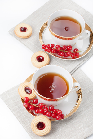 Tea served for two people on linen napkin on white background photo
