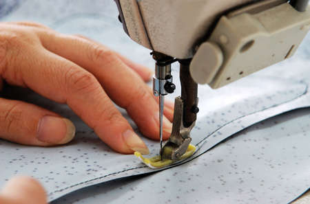 needlewoman: a worker is sewing with  bare hands