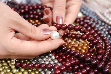 compare pearls on top of colorful freshwater pearl strands Stock Photo - 2158486