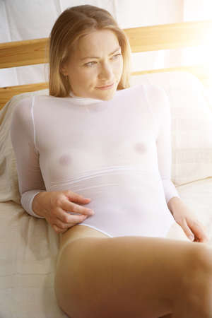 Attractive blonde woman wears body see through and transparent as lingerie or underwear in the bedroom