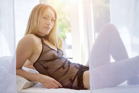 Attractive blonde woman wearing negligee see through and transparent as lingerie or underwear in the bedroom