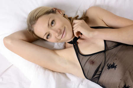 Pretty slim young woman wears negligee transparent and see-through as a nightdress, nightwear or underwear and lies in bed