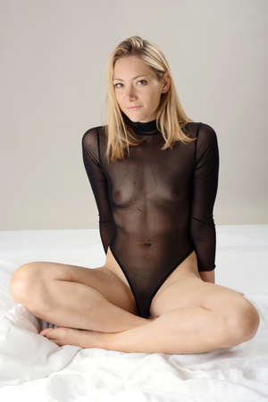Pretty slim young woman wears body transparent and see-through as underwear in the photo studio