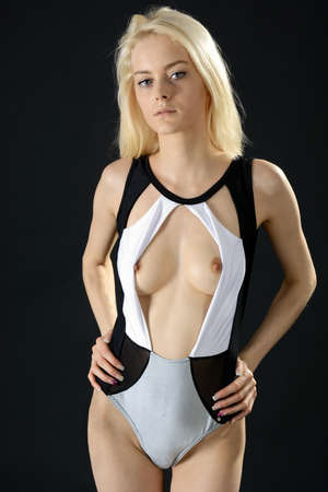 Beautiful slim blonde young woman posing with an open swimsuit in the photo studio