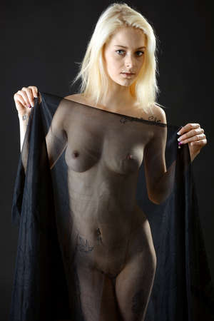 Gorgeous blonde young woman posing with transparent cloth in the photo studio