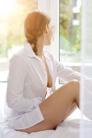 Attractive woman wears open blouse and sits relaxed on bed