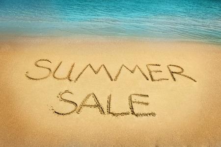 sommerferien: Summer sale Buchstaben auf dem Sand am Strand geschrieben Lizenzfreie Bilder