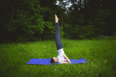 buena postura: Jovencita practicando yoga en el bosque en la alfombra p�rpura, Yoga-Salamba Sarvangasana �rbol de abedul