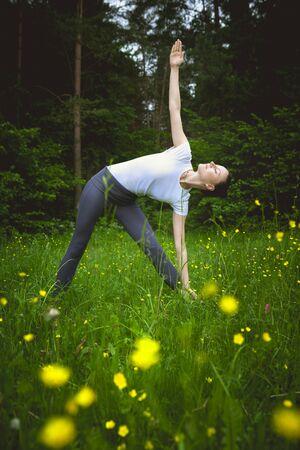 trikonasana: Yoga utthita trikonasana triangle pose by woman on green grass in the forest around nature
